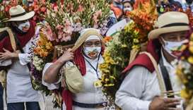 "Men an women carry flower arrangements known as ""Silletas"" at the ""Silleteros"" parade during Medelli"