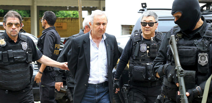 Businessman and rancher Jose Carlos Bumlai is escorted by federal police officers as he leaves the I