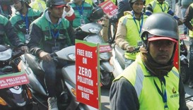 Civil defence volunteers use electric bikes to spread the message on day 1 of the implementation of
