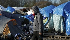 A migrant walks past shelters