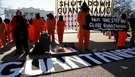 Protesters in orange jumpsuits from Amnesty International USA and other organizations rally outside