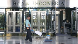 A worker cleans the entrance of the Bank Indonesia's headquarters in Jakarta. The central bank cut i