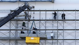 Men work near a crane at a construction site in Tokyo. Japan's core machinery orders tumbled the mos