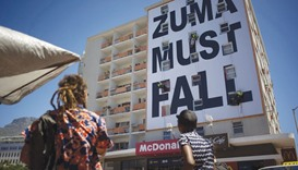 People watch as workers set up a giant banner referring the South African president in the trendy Lo