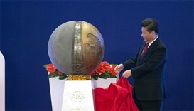 Chinese President Xi Jinping (C) unveils a sculpture during the opening ceremony of the Asian Infras
