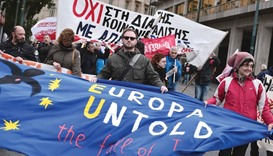 Demonstrators march and hold banners during a rally in central Athens yesterday, called by Greek mai