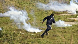 A migrant runs yesterday near clouds of tear gas in a field near Calais, France, as migrants gather