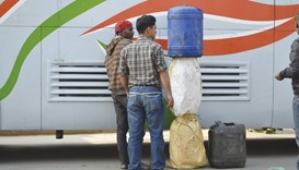 Men in Nepal's capital, Kathmandu, unload fuel smuggled over the border from India on a bus this mon