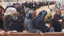 Syrian refugees stand in line as they wait for aid packages at Al Zaatari refugee camp in the Jordan