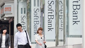 Pedestrians pass before a SoftBank mobile phone shop in Tokyo. The Japanese firm tumbled below the v