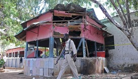 A policeman walks at the scene of an explosion at the Village Restaurant in Mogadishu yesterday.