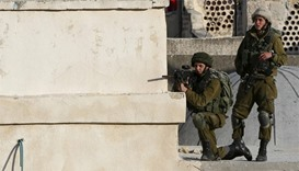 An Israeli soldier aims his weapon