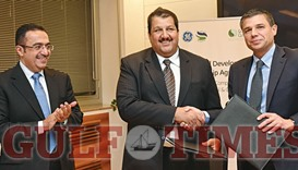 Al-Sowaidi (centre) shakes hands with Lorenzo Simonelli, president & CEO, GE Oil & Gas, after conclu