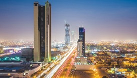 Light trails from traffic illuminate highways surrounded by residential buildings in Riyadh. Saudi A