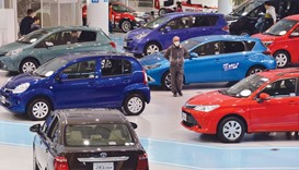 Customers check vehicles from Toyota at the company's showroom in Tokyo. The Japanese firm is likely
