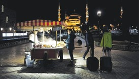 Foreign tourists stand next to a street vendor at Sultanahmet square in Istanbul on January 12. Tour