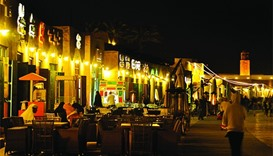 A man walks past customers of Souq Al Wakrah, which is gaining popularity for its scenic Corniche an