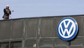 A worker stands next to a Volkswagen logo at a dealership in Madrid. Although US lawsuits are typica