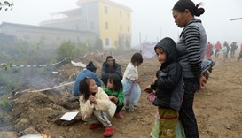 Refugees from Myanmar cooking outside a temporary shelter across the border in Manghai