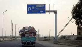 A pickup truck, filled with a family's belongings, leaves the border area in northern Sinai, where a