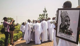 A family member carries a portrait of Rwanda's last king, Kigeli V Ndahindurwa, while others carry h