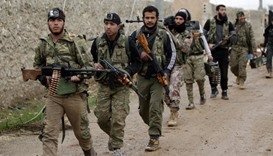 Rebel fighters walk carrying their weapons on the outskirts of the northern Syrian town of al-Bab.