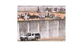 Police car drives past the wall of Alcacuz prison while inmates from different gangs protect themsel