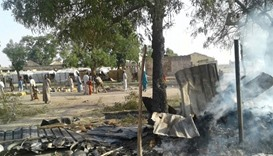 People walk at the site after a bombing attack of an internally displaced persons camp in Rann, Nige
