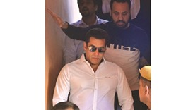 Bollywood actor Salman Khan walks with officials as he leaves after a court appearance in Jodhpur ye