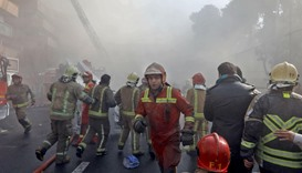 Firefighters stand at attention as dusts fills the air after the collapse of Iran's oldest high-rise