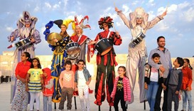 Stilt walkers dressed in colourful costume entertain young visitors. PICTURE: Ram Chand
