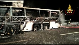 A still image taken from a video shows firefighters working next to a charred bus, which was carryin