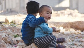 Children of war in Syria's Aleppo rest on the ruins of the city.