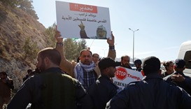 Palestinian protesters hold placards during a demonstration against the construction of Jewish settl