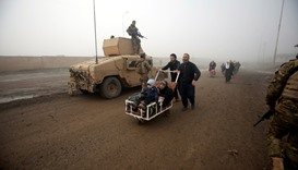 Displaced people pass Iraqi soldiers as they flee their homes during a battle with Islamic State mil