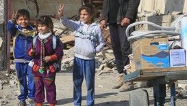 Children flash victory signs to Iraqi army soldiers during a fight with Islamic State militants nort