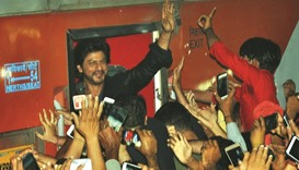 Actor Shahrukh Khan waves to fans at the Surat railway station.