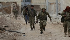 A rebel fighter runs with a weapon on the outskirts of the northern Syrian town of al-Bab, Syria Jan