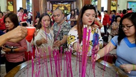 Members of the Chinese community light incense sticks as they offer prayers in Seng Guan temple