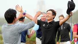 South Korea's Wang Jeunghun (R) celebrates upon winning the Qatar Masters golf tournament