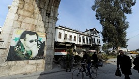 People walk past a picture of President Bashar al-Assad at Bab Sharqi entrance, near the Jobar distr