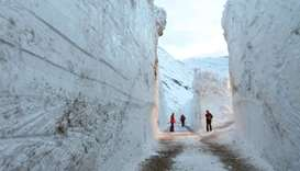 People looking at snow walls on the side of the street following the clearing up of the road due to