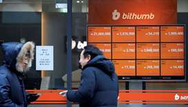 Men talk in front of an electric board showing exchange rates of various cryptocurrencies at Bithumb