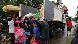 Residents with their belongings board a truck as they prepare to depart to the evacuation center aft