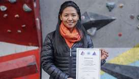 Nepali mountain guide Dawa Yangzum Sherpa posing with a mountaineering certificate in Kathmandu