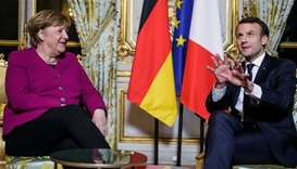 French President Emmanuel Macron and German Chancellor Angela Merkel react during their meeting at t