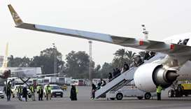Passengers disembark from their plane after landing at Mitiga airport