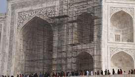 Tourists visiting the Taj Mahal near scaffolding installed for the conservation work at the monument