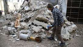 A man is seen near the remains of a rocket in Douma, Eastern Ghouta in Damascus, Syria