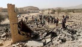 People gather at the site of an air strike that destroyed a house on the outskirts of the northweste